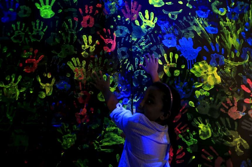 A girl looks back while adding to handprints for a cause on a neon board during the Earth Hour in Pasay city, metro Manila.