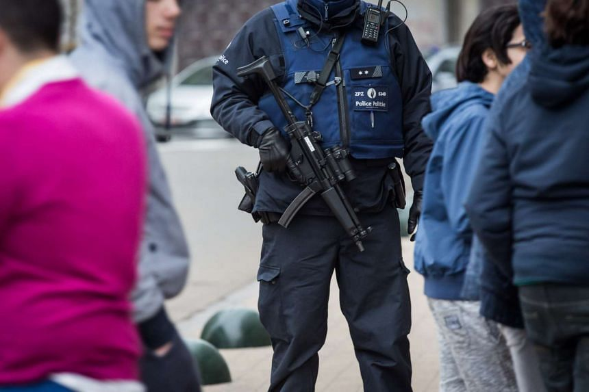 A Belgian police officer stands guard during the police action in Molenbeek on March 18, 2016.