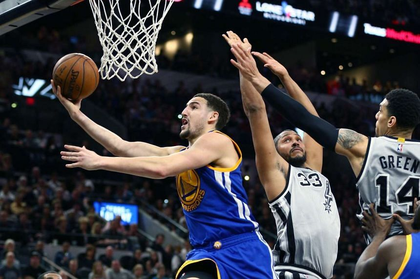 Golden State Warriors guard Klay Thompson (left) shoots against the San Antonio Spurs at the AT&T Center on March 19, 2016.