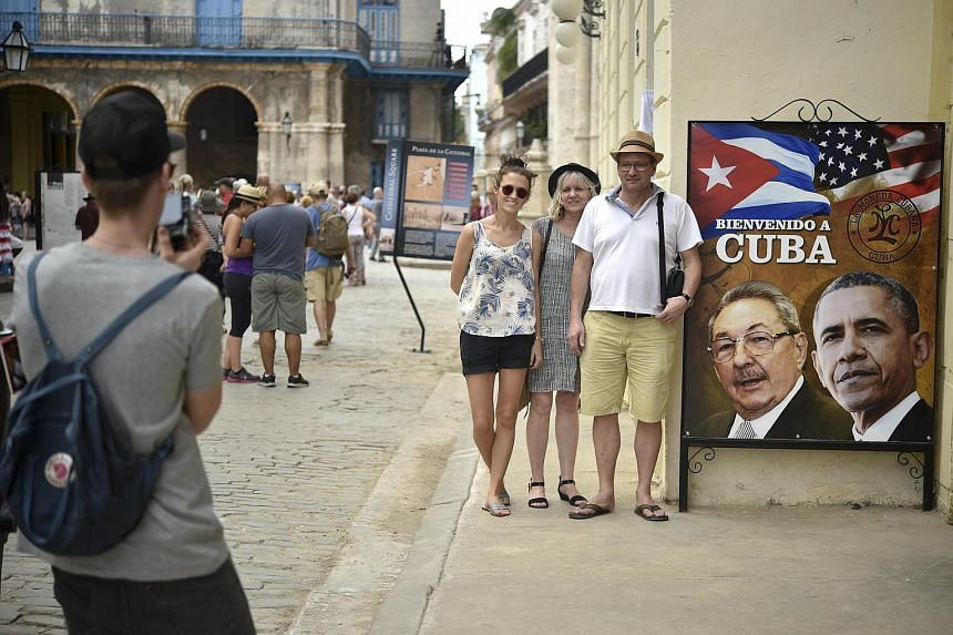 Tourists pose next to a sign with the images of Cuban and US Presidents Raul Castro and Barack Obama in Cuba, on March 19, 2016.