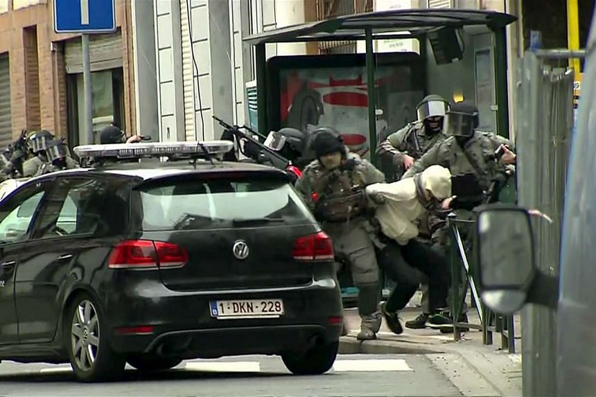 Armed Belgian police apprehend a suspect, in this still image taken from video, in Molenbeek, near Brussels on Friday (Mar 18) but there was no confirmation this was Salah Abdeslam,