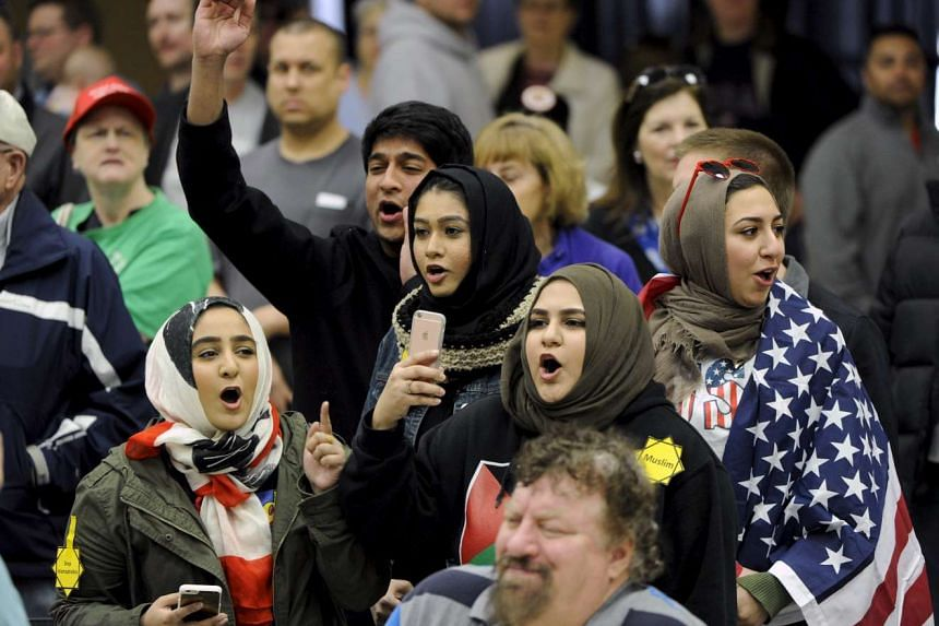 (Above) Young Muslims protesting against Mr Trump before being escorted out of a campaign rally in Wichita, Kansas, earlier this month.