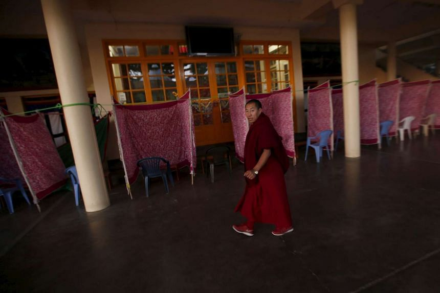 A Tibetan monk walks past temporary polling booths inside the Tsuglakhang temple in Dharamsala, India, on March 19, 2016.