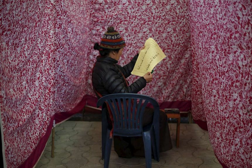 A Tibetan exile checks her ballot paper before casting her vote at a polling booth in Dharamsala, India, on March 20, 2016.