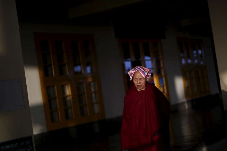 A Tibetan nun walks inside the Tsuglakhang temple in Dharamsala, India, on March 19, 2016.