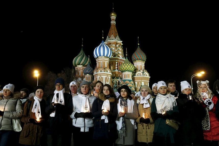 Performers for Earth Hour hold candles as they commemorate the victims of the crashed Boeing 737-800 flight FZ981 in Moscow, on March 19, 2016.