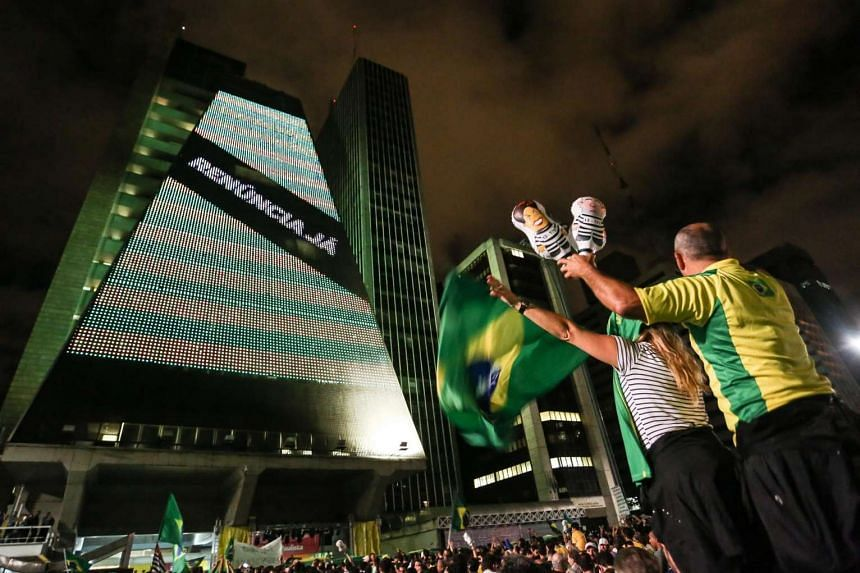 A large screen displays a message reading 'Resign Now' as demonstrators protest against the appointment of the former President Luiz Inacio Lula da Silva as Chief of Staff, at the Paulista Avenue in Sao Paulo, Brazil, on March 16, 2016.
