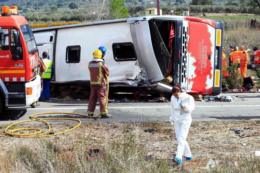 Emergency personnel operate on the Spanish AP-7 motorway near Freginals, Amposta south of Tarragona following a fatal bus accident that claimed the lives of 14 foreign students an injured 43 others early on March 20, 2016.