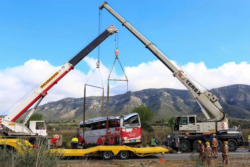 Emergency personnel look on as two cranes hoist a bus onto a trailer on the Spanish AP-7 motorway near Freginals, Amposta south of Tarragona following a fatal accident that claimed the lives of 13 foreign students an injured 44 others early on March