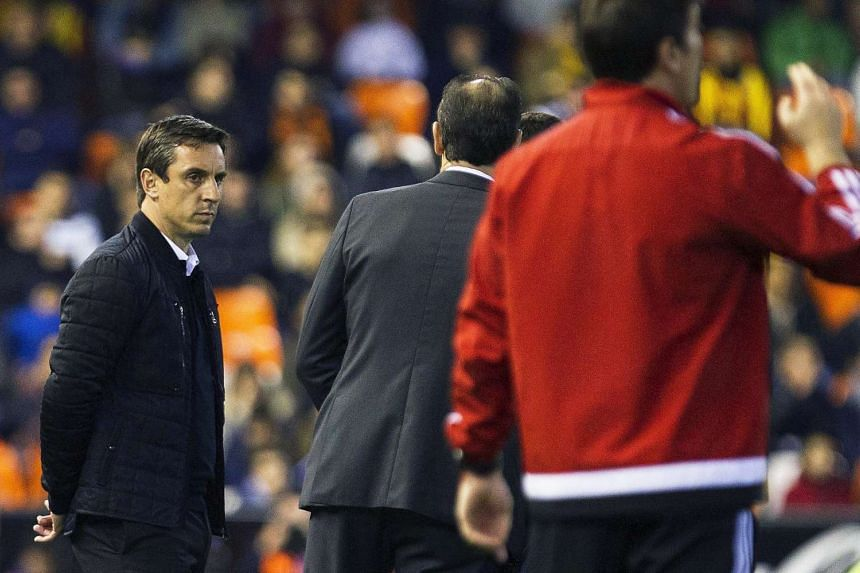 Valencia's English head coach Gary Neville (left) reacts during the Spanish Primera Division soccer match between Valencia CF and Celta Vigo at Mestalla stadium in Valencia, eastern Spain, on March 20, 2016.