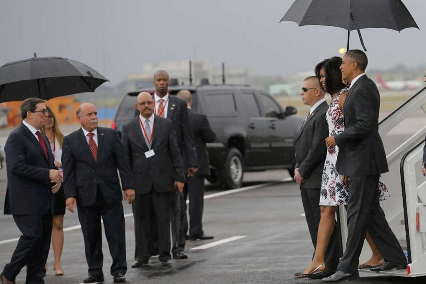 US President Barack Obama and his wife Michelle approach Cuba's foreign minister Bruno Rodriguez (left) as they arrive at Havana's international airport for a three-day trip, in Havana on March 20, 2016.