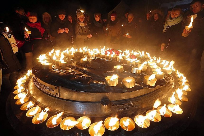 People lighting candles in central St Petersburg in memory of those who died when a Flydubai plane crashed during landing at the Rostov-on-Don airport in southern Russia, last Saturday. The Boeing 737-800 jet operated by the United Arab Emirates-base