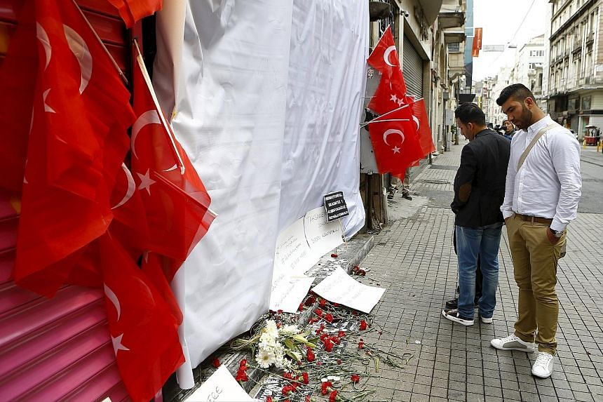 Tributes for victims at the site of the blast in Istiklal street, a major tourist area in central Istanbul, yesterday. Turkish Interior Minister Efkan Ala identified the bomber as Mehmet Ozturk. DNA testing matched samples from Ozturk's father, who l