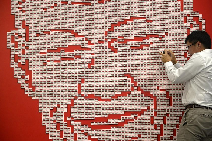 Mr Shaun Lee, nephew of the late Mr Lee Kuan Yew, taking a photo yesterday of the art installation made up of 4,877 Singapore flag erasers put together to form his uncle's image. The installation at The Red Box in Somerset Road was constructed by som