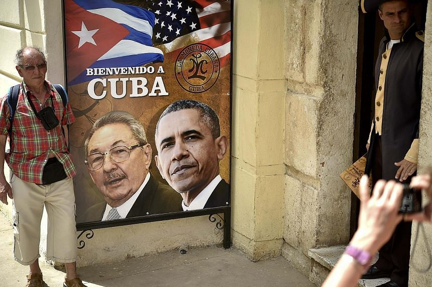 A tourist in Havana posing with a poster carrying the images of Cuban President Raul Castro and his American counterpart Barack Obama on Saturday. Mr Obama arrived in Cuba yesterday.