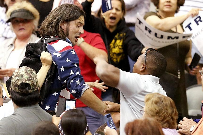 A protester (in blue) being attacked by Trump supporters while the billionaire candidate was giving a speech at a campaign event in Tucson, Arizona on Saturday.
