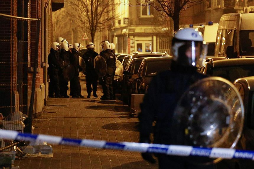 Belgian security forces seal off an area during an anti-terror operation in the Molenbeek neighborhood of Brussels, Belgium.