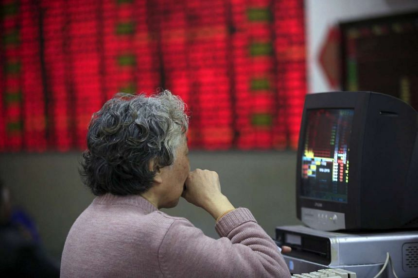 An investor looking at stock information at a brokerage house in Shanghai, China, on March 14, 2016.