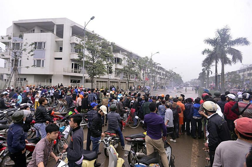 People gather outside the site of an explosion in Ha Dong District, in Hanoi, Vietnam, on March 19, 2016.