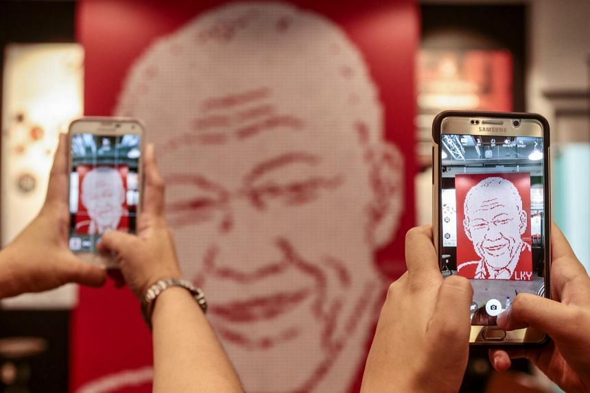 Visitors take photographs with their mobile phones of a mural made out of nearly 5,000 Singapore country erasers forming the likeness of Mr Lee Kuan Yew.
