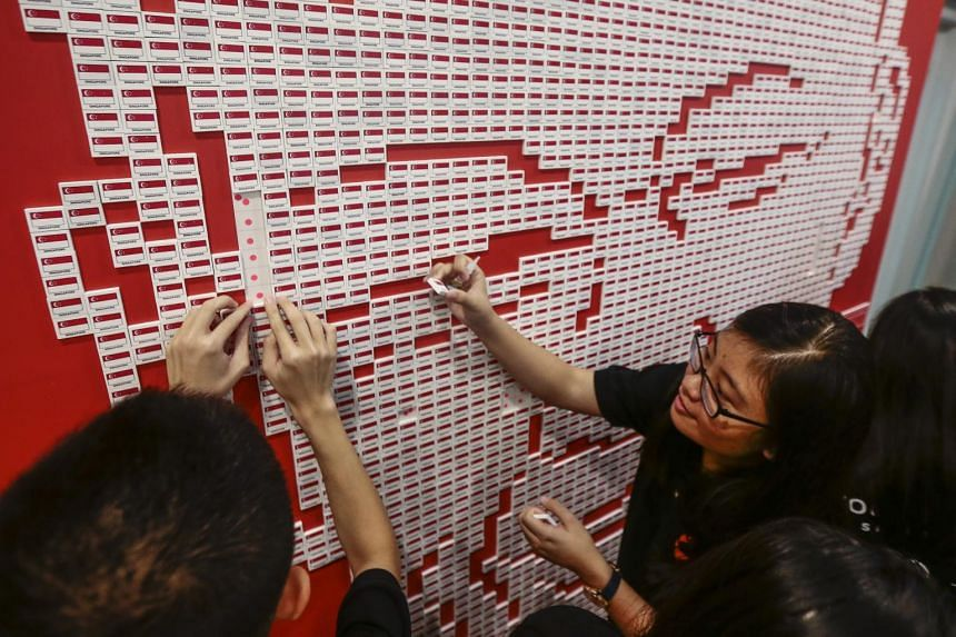 Youth volunteers placing erasers bearing the flag of Singapore to form a mural of Mr Lee Kuan Yew.