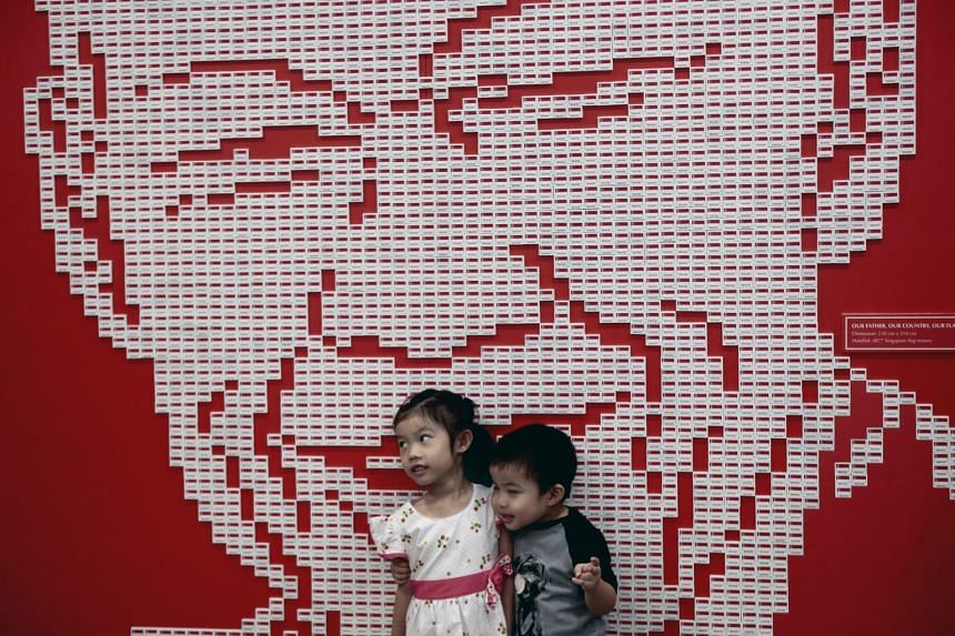 Two young children pose for a photograph against a mural made out of nearly 5,000 Singapore country erasers forming the likeness of Mr Lee Kuan Yew.