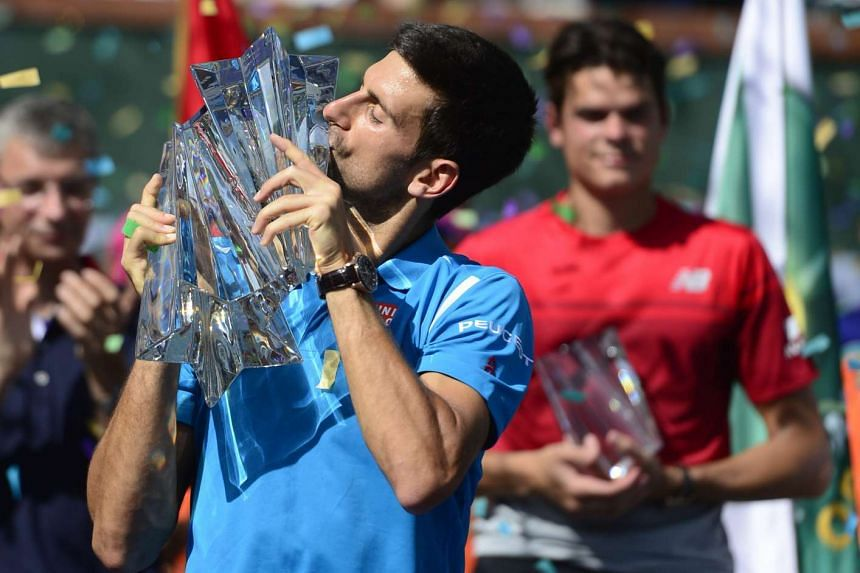 Novak Djokovic (left) kisses the trophy after defeating Milos Raonic during their final match at the BNP Paribas Open tennis tournament in Indian Wells.