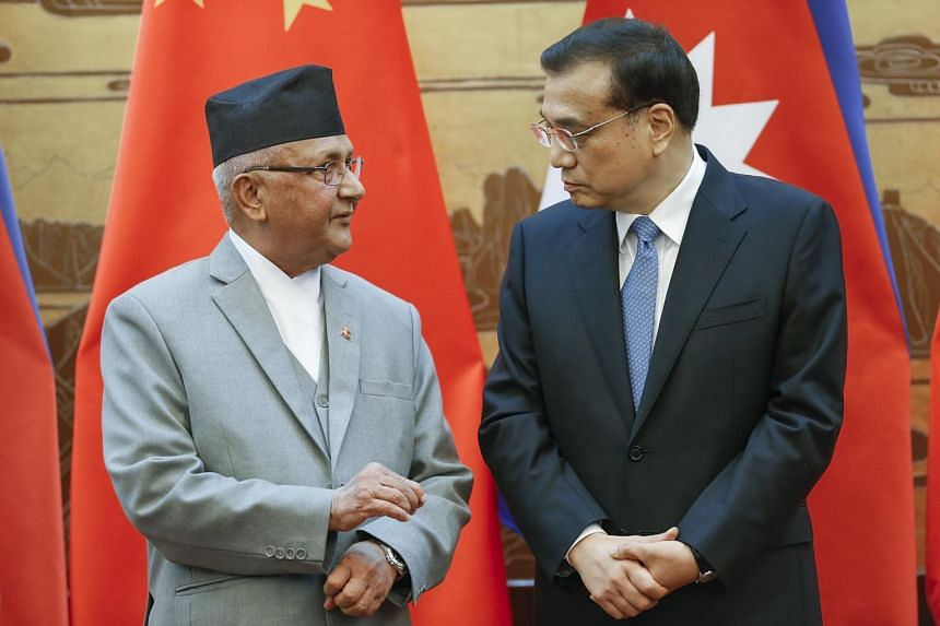 Chinese Premier Li Keqiang (right) talks to Nepal Prime Minister Khadga Prasad Sharma Oli at the Great Hall of the People in Beijing on March 21, 2016.
