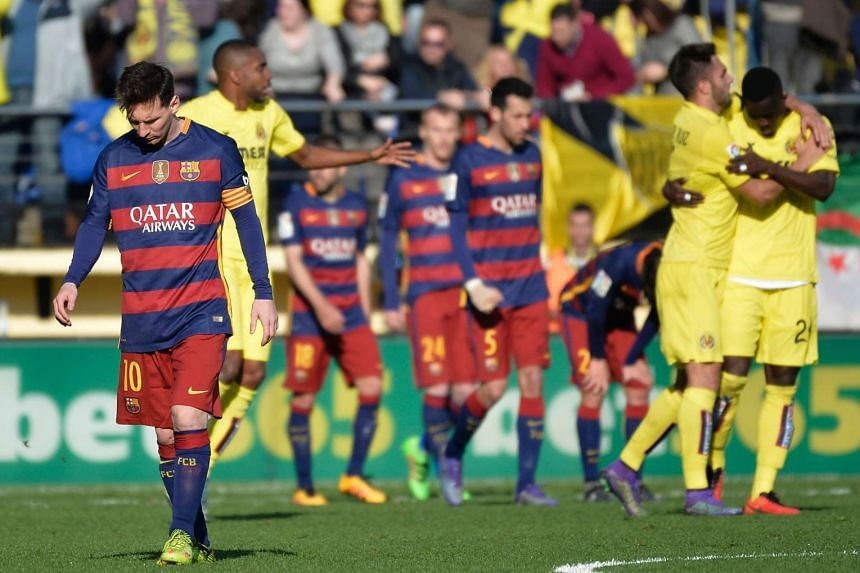 Villarreal (right) players celebrate their second goal as Barcelona forward Lionel Messi walks away during the Spanish league football match at El Madrigal stadium on Sunday (March 20).