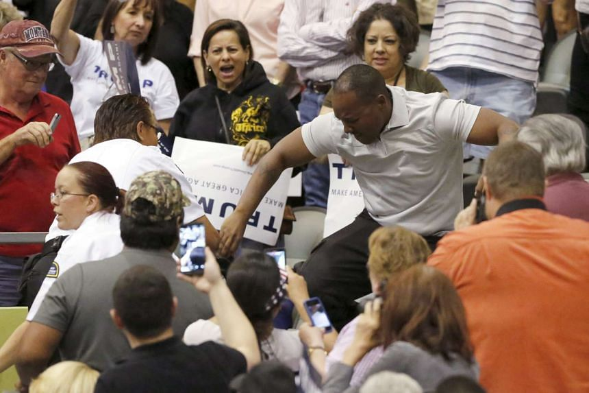 A Donald Trump supporter (right) kicks and stomps on a protester as the Republican presidential candidate speaks at a campaign event in Tucson, Arizona on Saturday (March 19).