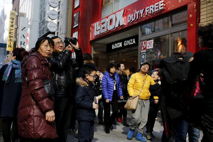 Chinese tourists stand outside a tax free department store in Tokyo, Japan, on Feb 4, 2016.