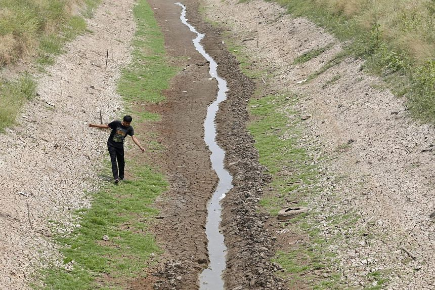 A Thai villager walking alongside an almost dried up irrigation canal in Chachoengsao province, Thailand, on March 6, 2016.