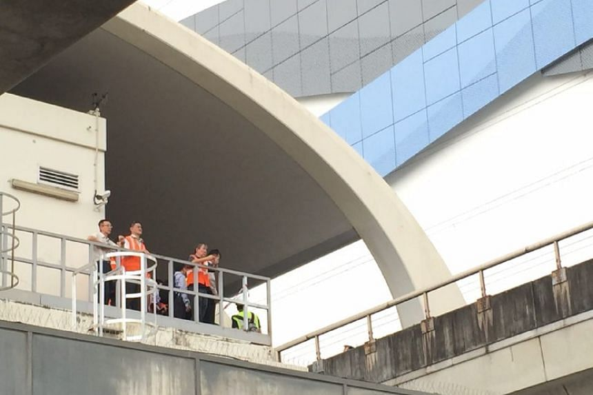 SMRT staff members assessing the situation on the train tracks at Pasir Ris MRT station.