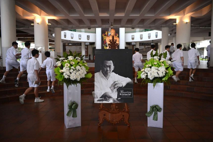 Raffles Institution students walk pass a portrait of the late Mr Lee Kuan Yew at the school's atrium before assembly on March 22, 2016.