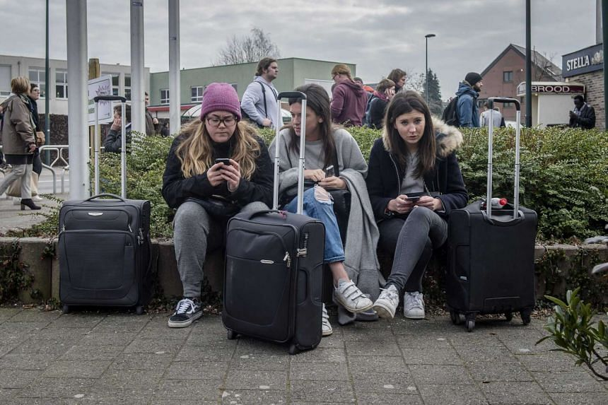 Stranded passengers wait with their luggage near Brussels airport in Zaventem, Belgium.