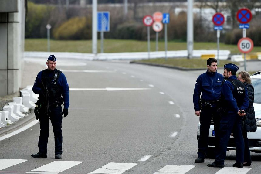 Belgian police officers patrol at Brussels Airport in Zavedam following twin blasts on March 22, 2016.