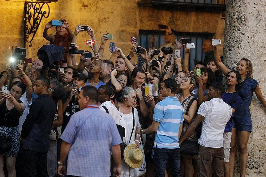 Tourists and local residents taking pictures during the visit of Mr Obama to Old Havana on Sunday. US President Barack Obama and Cuban President Raul Castro in their first meeting on the second day of the American leader's visit to Cuba. Mr Obama is