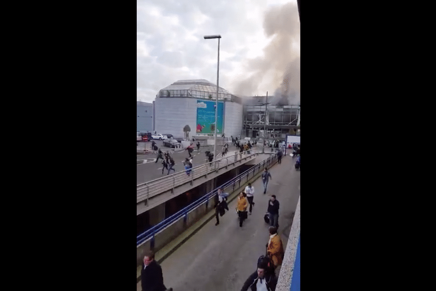 People running out of the Brussels airport with visible smoke trailing from the building.