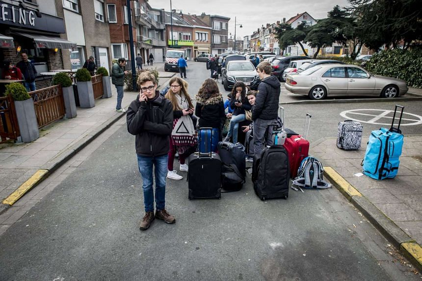 Passengers wait with their luggage near Brussels airport in Zaventem, Belgium, on March 22, 2016.