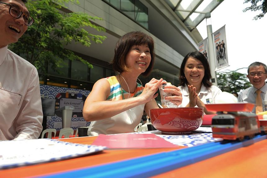 Dr Amy Khor taking part in the demonstration of the Lite Lunches Programme conducted by NUS Save members.