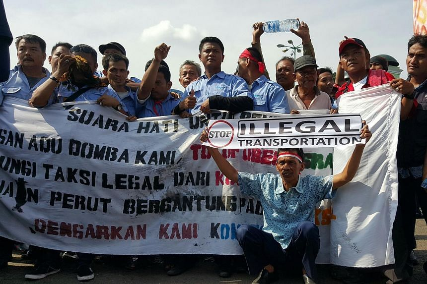 Cabbies and drivers of three-wheeled bajajs crowding outside of Indonesia's Parliament and the Information and Communication Technology Ministry, on March 22, 2016.