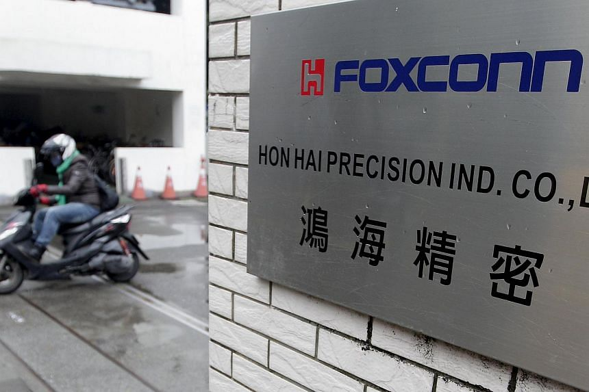 A file photo of a motorcyclist riding past the entrance of the headquarters of Foxconn, formally known as Hon Hai Precision Industry Co, in Taipei.