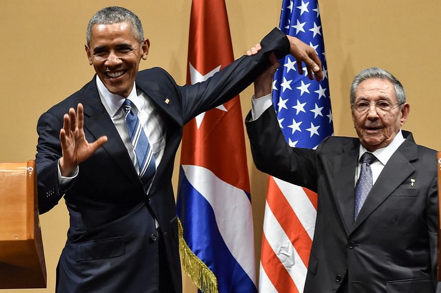Cuban President Raul Castro (right) raises US President Barack Obama's hand during a meeting at the Revolution Palace in Havana on March 21, 2016.