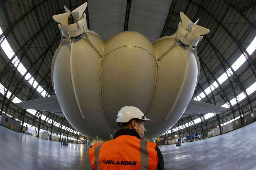 A worker stands under the Airlander 10 hybrid airship during its unveiling in Cardington, Britain on Monday (March 21).