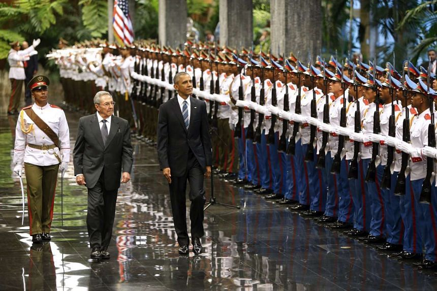 US President Barack Obama (second from left) and Cuban President Raul Castro review the troops at the Revolution Palace in Havana on Monday (March 21).