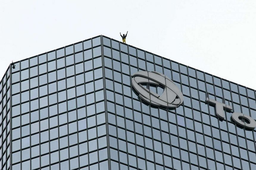 Alain Robert waves after reaching the summit of a building above the Total offices near Paris on Monday, March 2l.