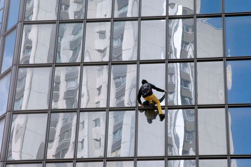 Alain Robert climbs a building hosting the headquarters of French oil giant Total on Monday (March 2l) in Courbevoie, a Paris suburb.