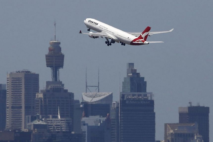 A Qantas Airways Airbus A330-300 jet takes off from Sydney International Airport over the city skyline.