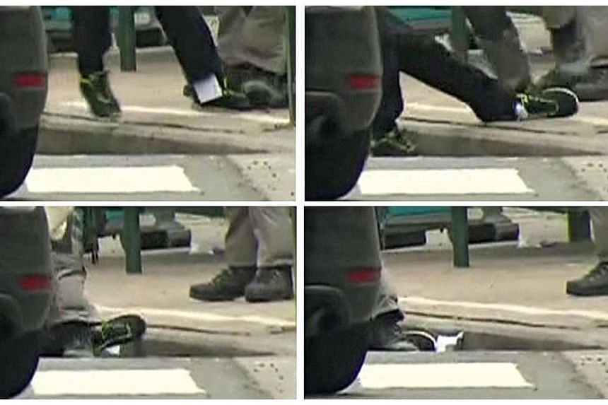A combination of images taken from a video showing a piece of paper falling from Salah Abdeslam's trousers as he was captured by police, in Molenbeek, near Brussels, on Friday.