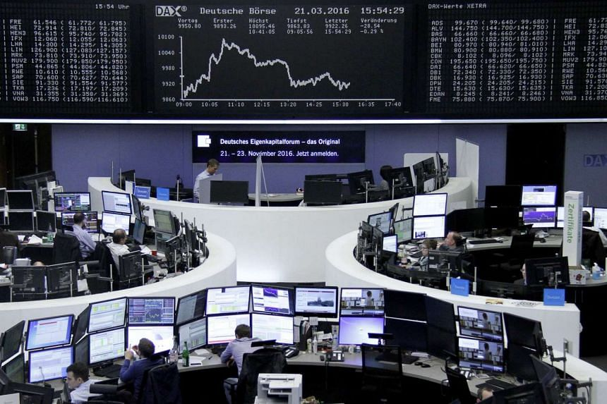 Traders work at their desks in front of the German share price index, DAX board, at the stock exchange in Frankfurt.